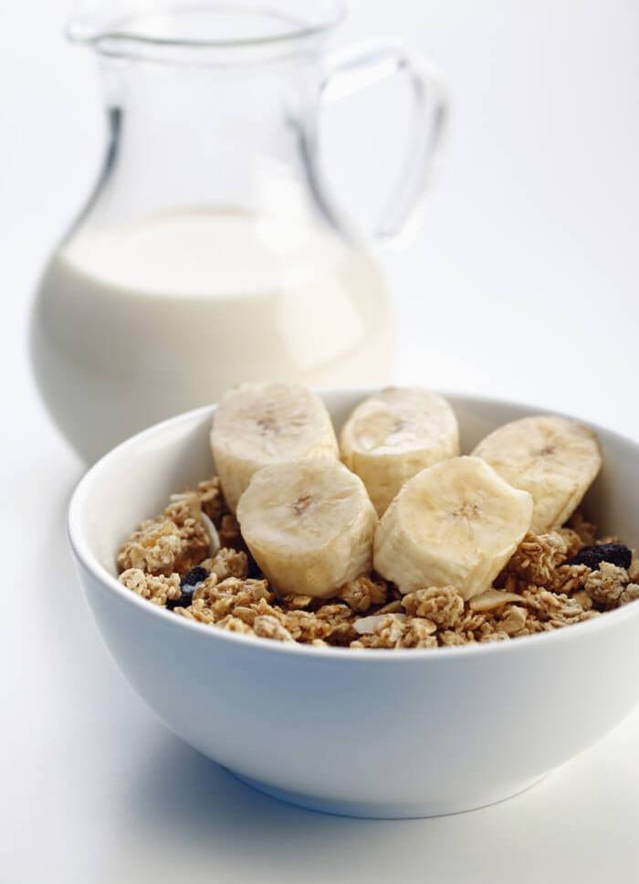 healthy food items in a bowl that are rich in carbohydrates and protein. like: milk in a jug; bananas, oats, cereals, etc. in a bowl