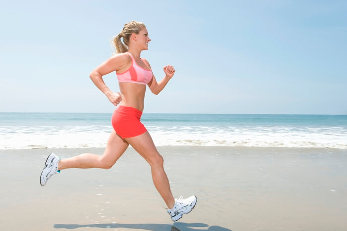 sporty woman running with a smile on a beach wearing running outfit and running shoes