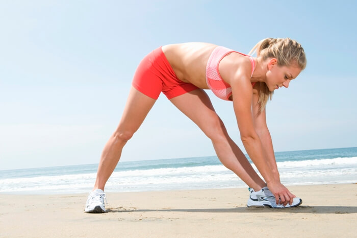 sporty woman stretching and warming up before a run on a beach wearing running outfit and running shoes