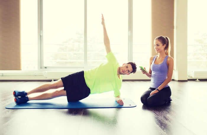 man doing side plank leg raise while a smiling woman sitting besides watches and keeps time on her phone