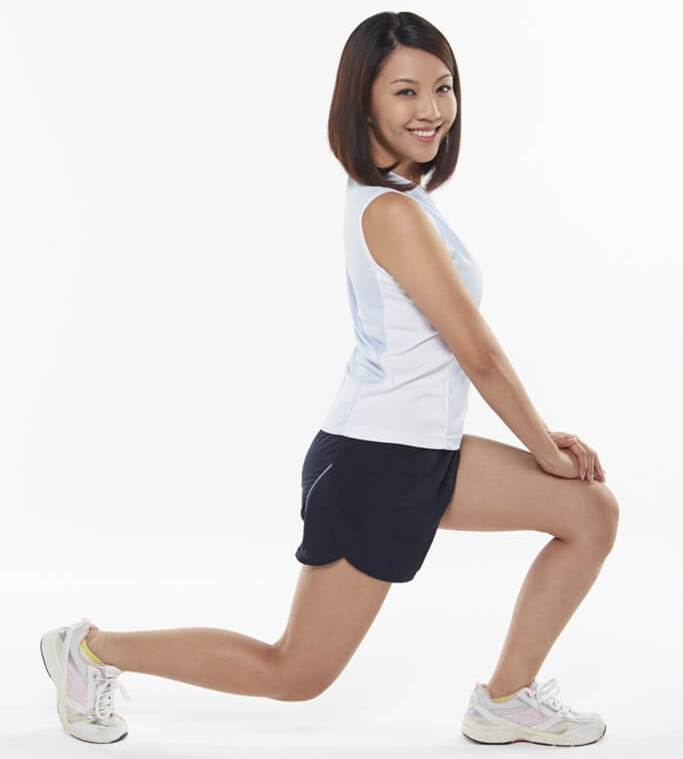 smiling woman doing lunges exercise and stretching