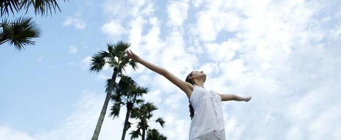 Woman feeling refreshed and lively while her hands are raised in the air towards the sky.