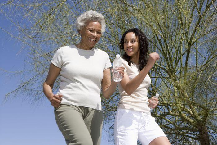 Woman running with her smiling, cheerful grandmother: Depicting a healthy body and mind in the old age.