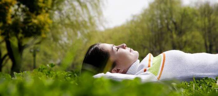 A calm and relaxed woman lying on her back in a park on a bright sunny day.