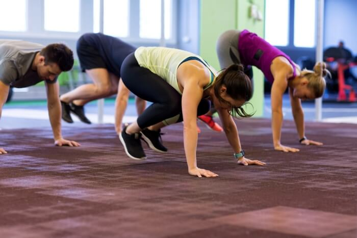 group of people doing burpees shown in jumping squat position