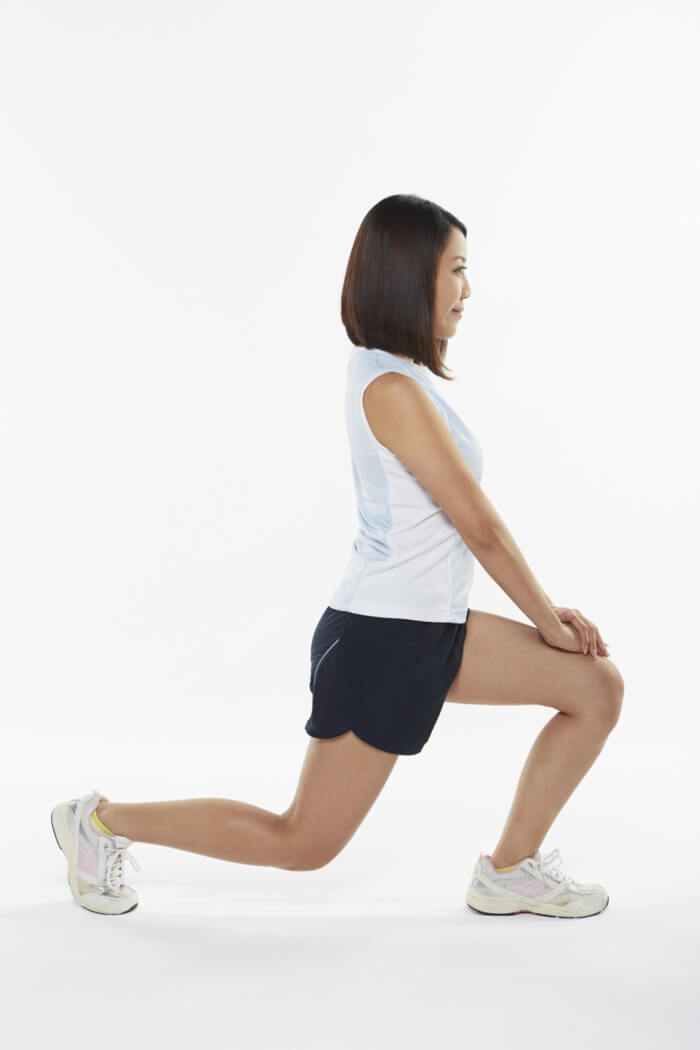 Woman doing lunges in sports outfit: side pose