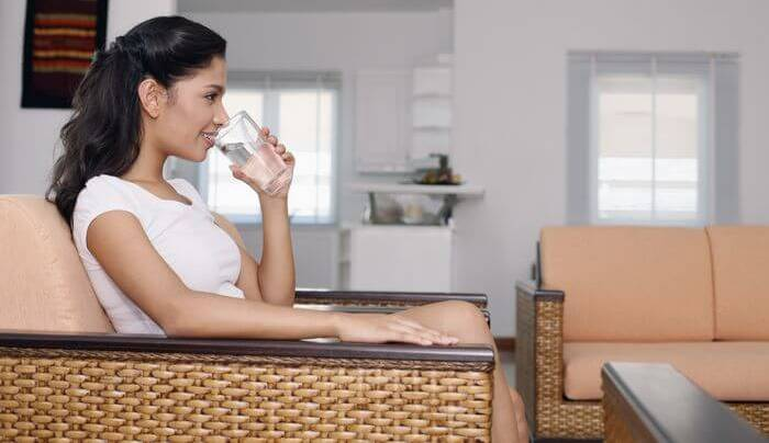 Woman drinking water while sitting on a couch.