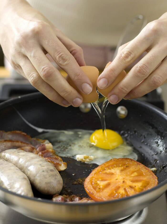 Man preparing a protein rich diet (eggs, sausages, etc.) in a frying pan.