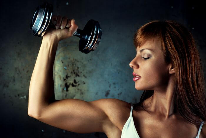 Fit, slim and muscular women is checking her arms while holding a dumbbell in one hand: Showing her low body fat and more muscle mass.