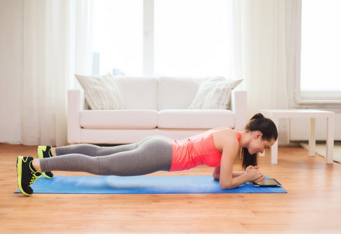 fit and slender woman doing plank to tone up the abdomen: at home, in sports outfit