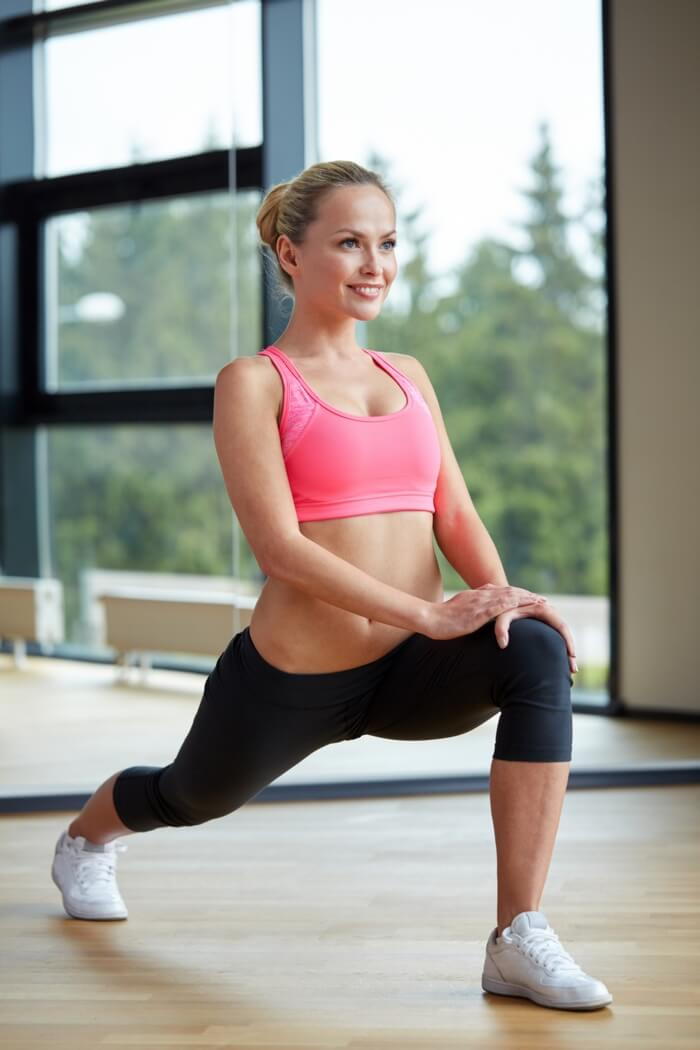 slim, slender, sporty and smiling woman doing lunges for strengthening and toning hamstrings, calves and thighs: