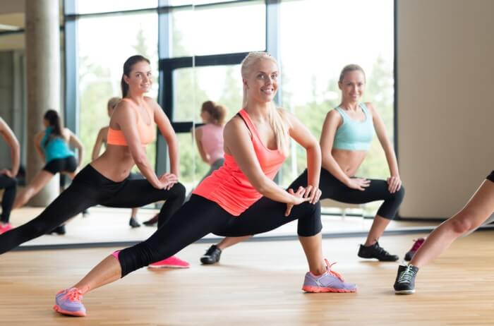 sporty women doing lateral lunge side kick in a gym: to strengthen and tone up the lower body.
