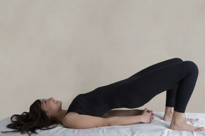 smiling, young, sporty and slim woman performing hip bridge while hands on floor: to tone up lower back and hips.