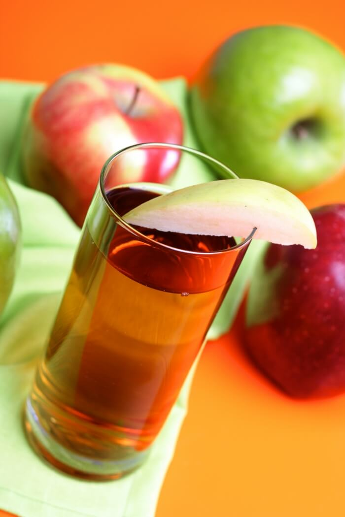 Glass filled with apple cider vinegar and apples (red & green) are placed around it.