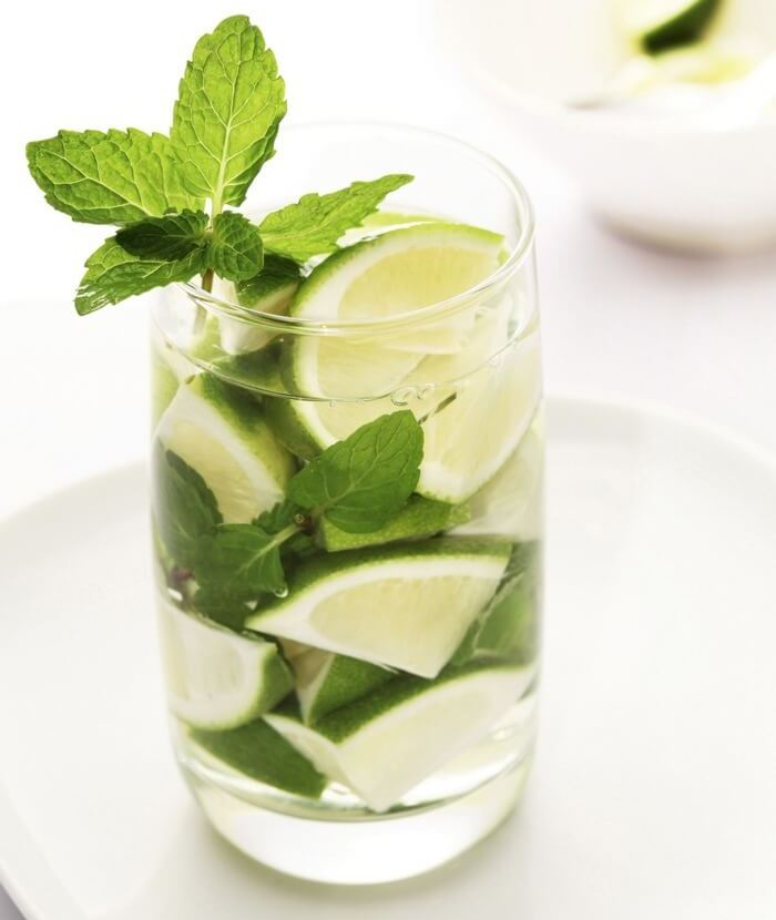 Glass filled with detox water (water, lime juice & slices, mint leaves)