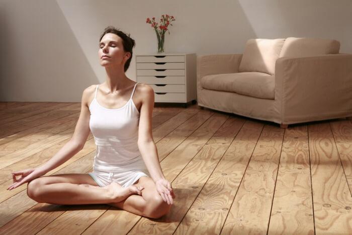 Woman doing kapalbhati yoga (breathing exercise) at home, while sitting in padmasana