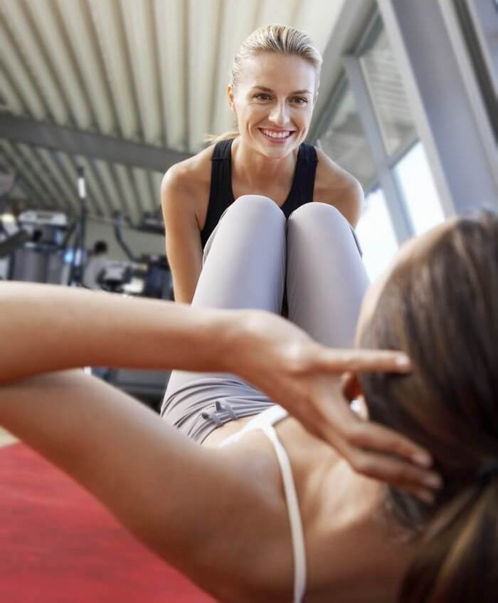 Woman doing crunches while another woman assists her by holding her legs, in a gym