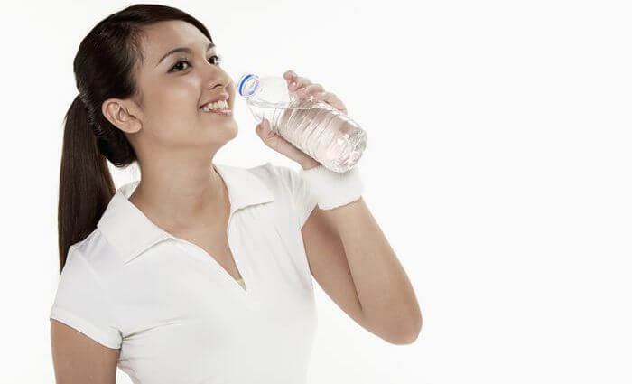 Woman drinking water from a water bottle.