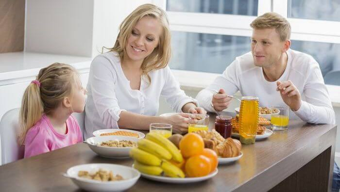 Family sitting on a table with healthy breakfast (fruits, cereals, juices, etc) placed on the table.