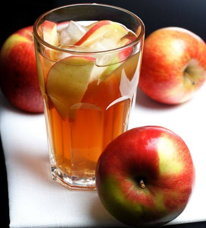 Glass filled with apple cider vinegar and apples are placed around it.