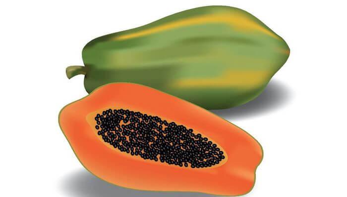 Close up of whole and sliced papaya.