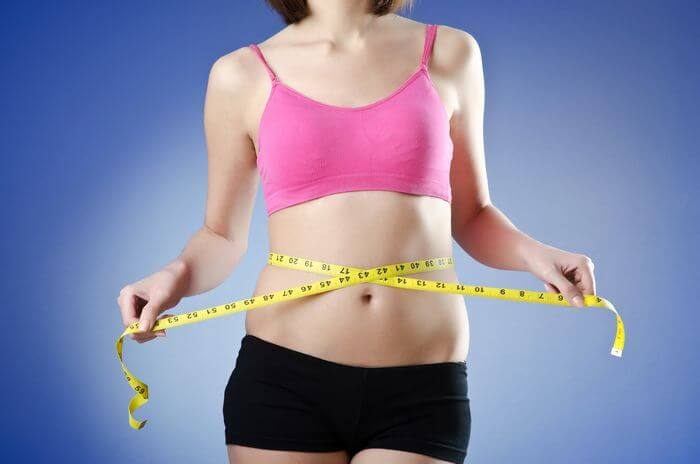 Healthy and fit woman measuring her flat belly with a measuring tape.