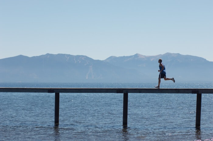 Man running a long distance run along a long road-bridge with mountains in the background.