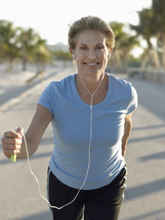 Slightly older woman running while listening to music and holding an mp3 player in her hand.