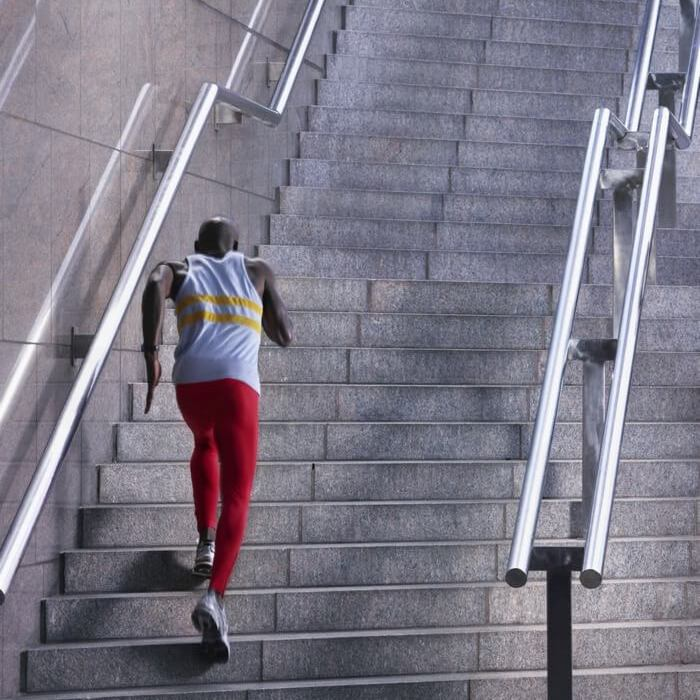 Athletic, young man running up the stairs to increase performance, strength, speed  and stamina.