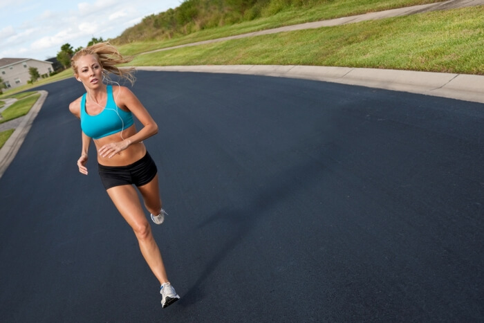 Fit, healthy, young woman running fast and long distance on a road, dressed in sports outfit.