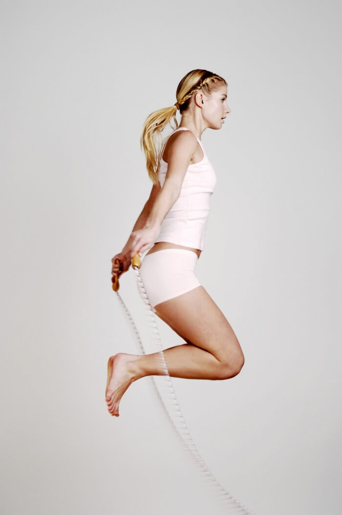 Woman jumping high with a skipping rope, like in a froggy jump.