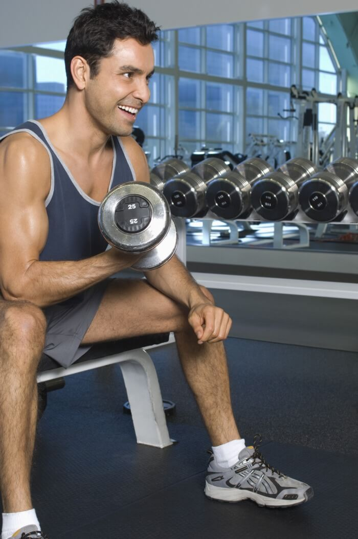 Fit and healthy man doing weight training in a gym to increase strength, speed and stamina.