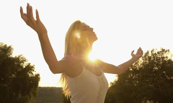 Woman is outdoor with sun on top at noon time.