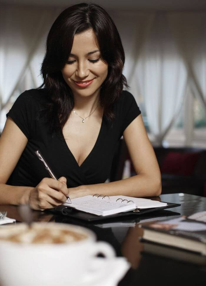 Woman writing with a pen in a notebook: Depicting writing down a plan in diary.