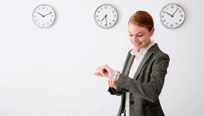 Woman taking time on her wrist watch, while clocks hang on the wall in the background.