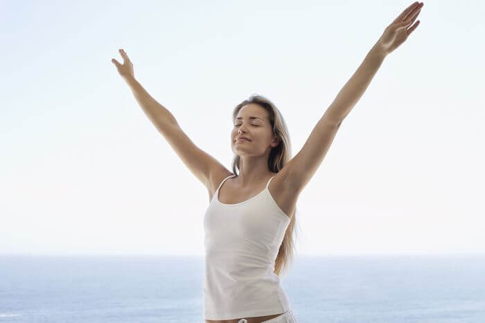 Woman outdoor, feeling happy and relaxed with her arms raised.
