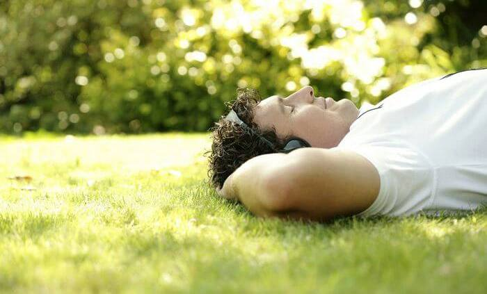 Relaxed man lying peacefully with his back on the grass, listening to music with eyes closed while just being with himself.