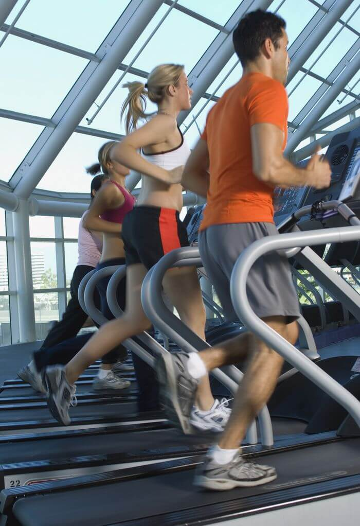 People running on a treadmill in a gym.