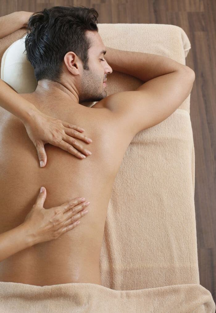 Back of a man being massaged by a women while he is lying on his abdomen.