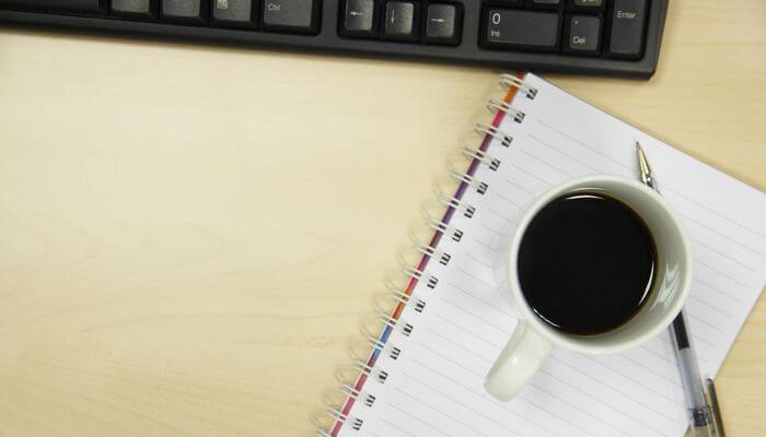 A cup filled with coffee placed on a notebook on a table.