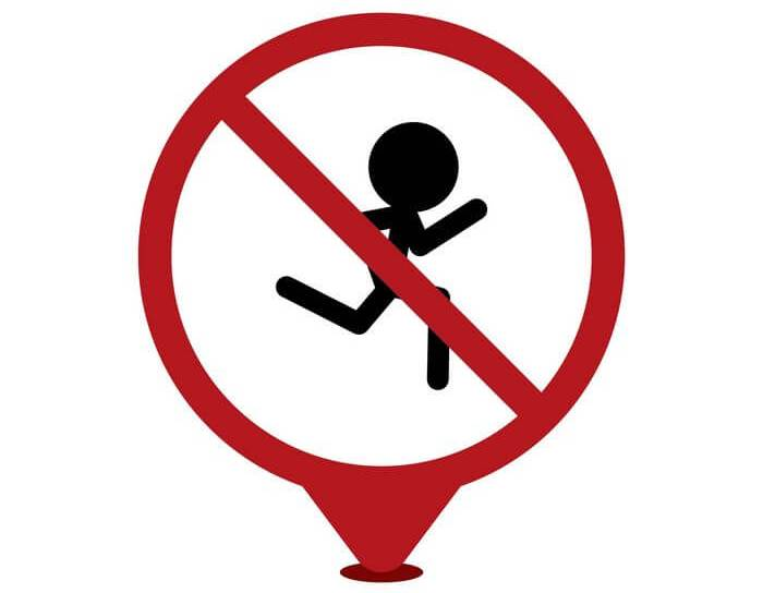 A road sign with a red circle and strike through the center of a running icon: Depicting running prohibited.