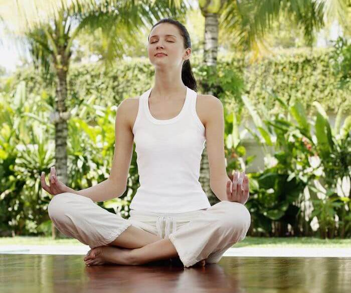 Close up of a woman meditating while sitting on the floor, with green background.