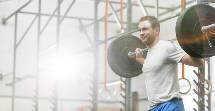 Man lifting heavy weights in a gym.