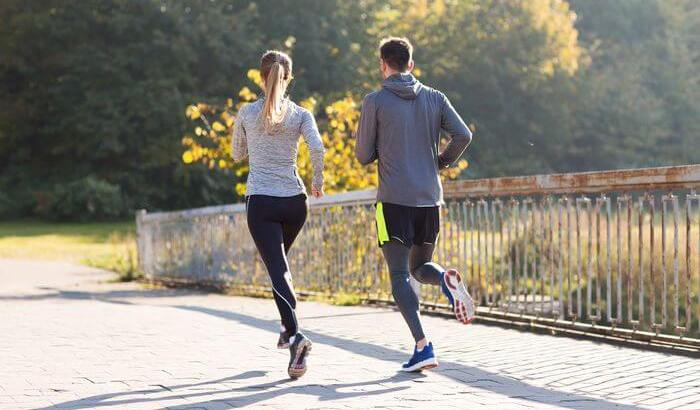 Healthy and fit man and woman running, while wearing running outfit.