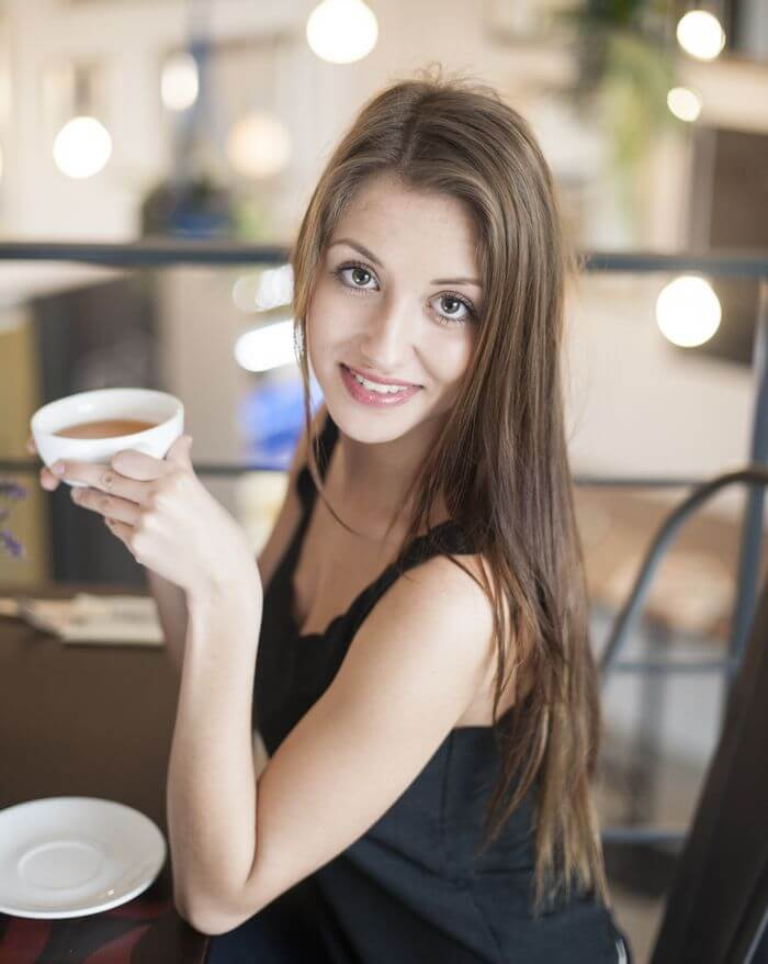 Woman drinking coffee while holding the cup in hand