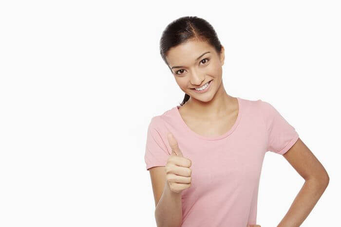Smiling woman with positive attitude while showing thumps up