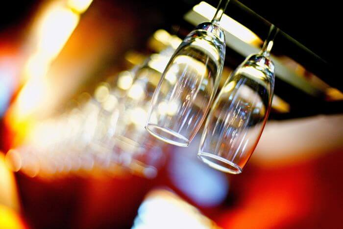 Glasses hanging from a stand in a bar with bright party lights in the background.