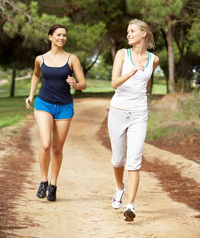 Two woman running and going along while looking and smiling at each other