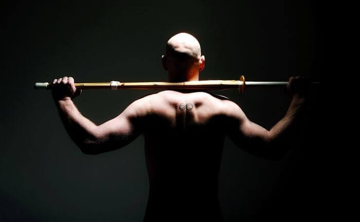 Close up of the back side of a man doing strength training.