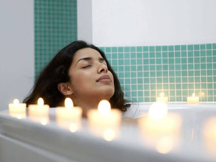 Woman relaxing with eyes closed in a bath tub with candles placed around the tub.